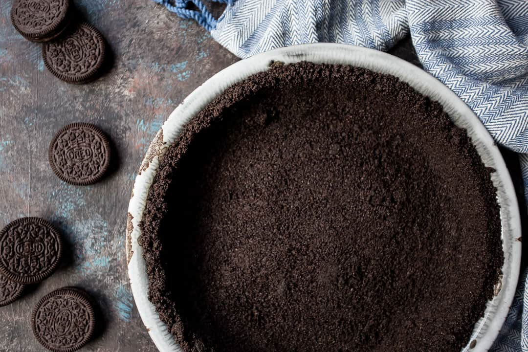 Oreo crust for pie or cheesecake, on a dark background with a blue towel.