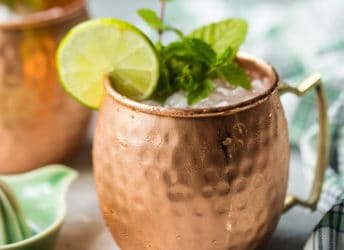 An icy Moscow mule drink in a copper mug, garnished with lime and fresh mint.