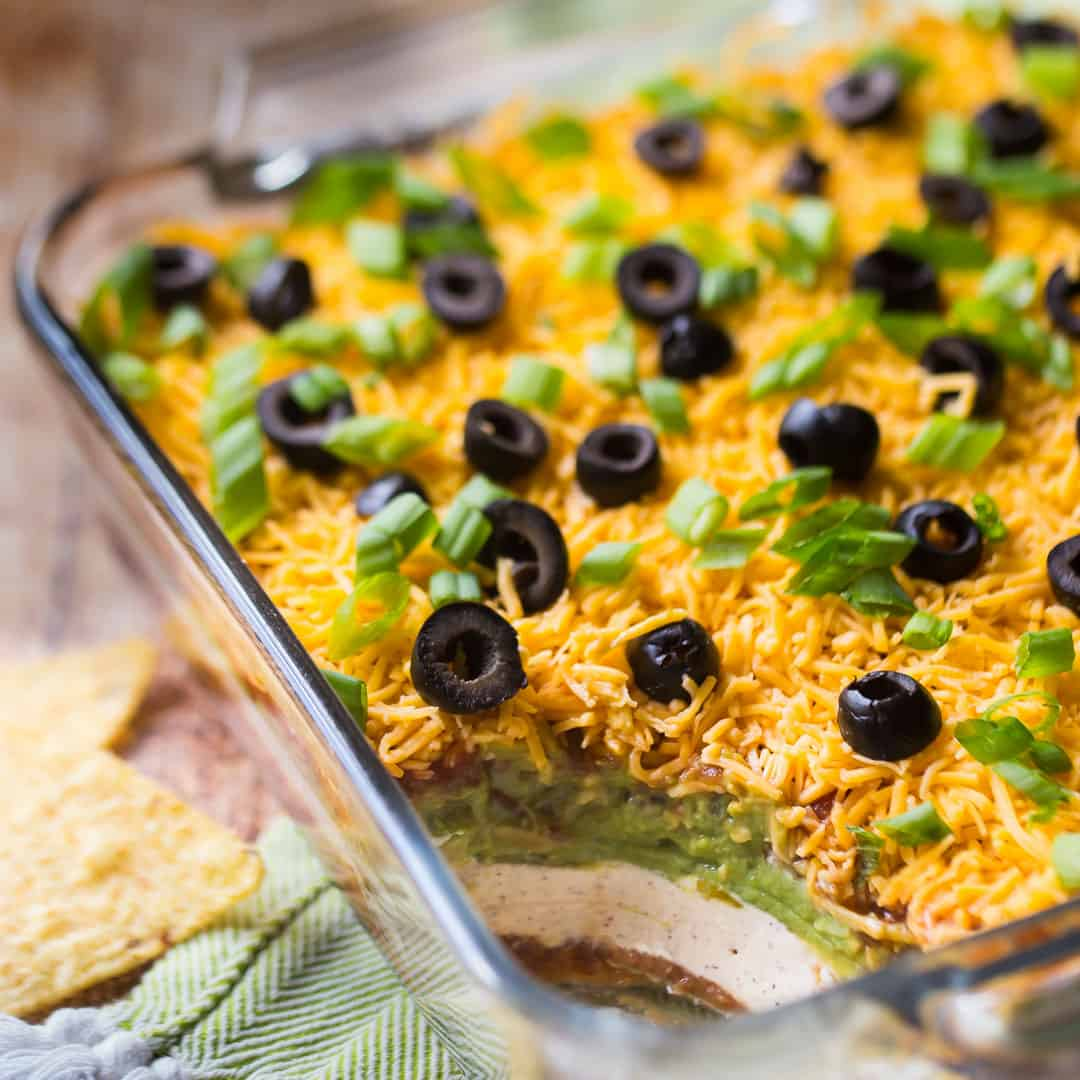 7-Layer dip in a square glass dish, with a green napkin.