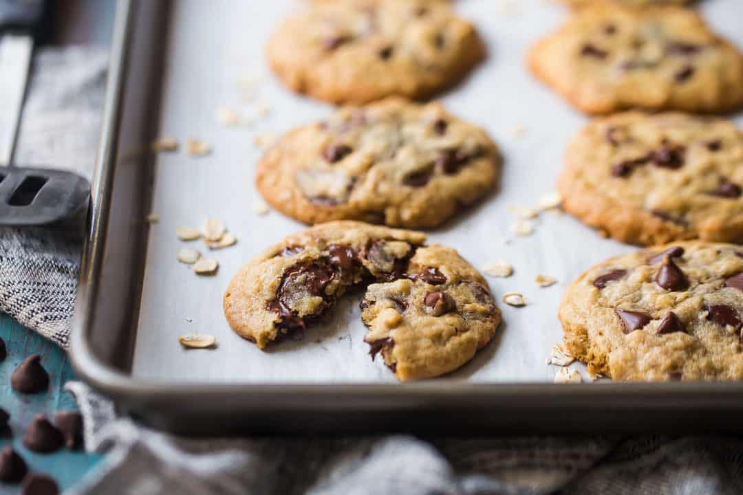 Healthy oatmeal chocolate chip cookies on a parchment-lined tray with oats and chocolate chips.