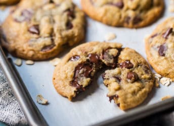 Close up image of a freshly baked oatmeal chocolate chip cookie, broken in half to reveal melting dark chocolate.