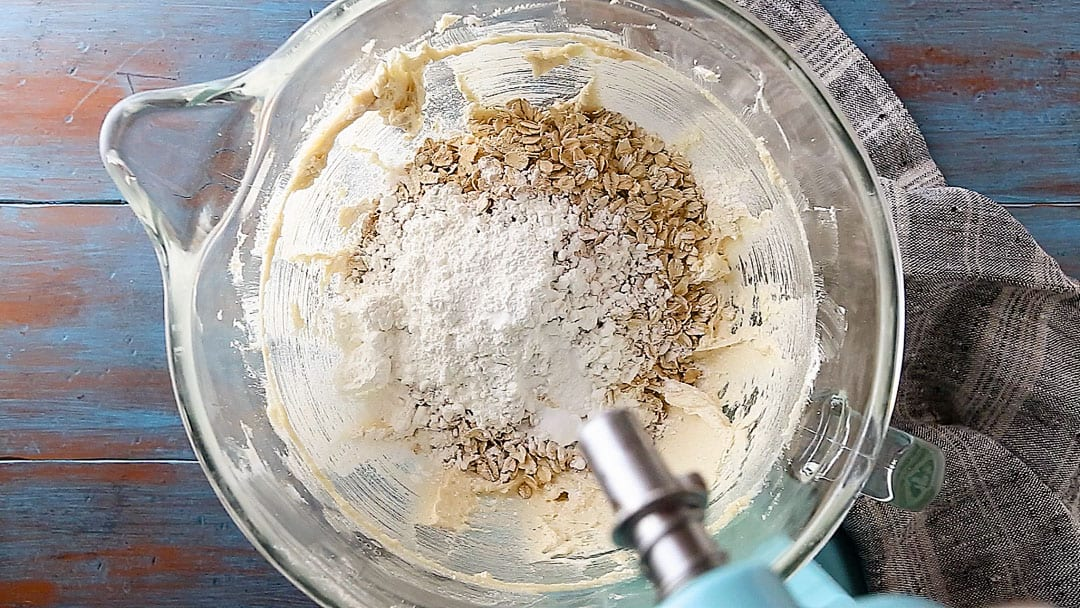Adding flour, oats, cornstarch, baking soda, and salt to cookie dough.