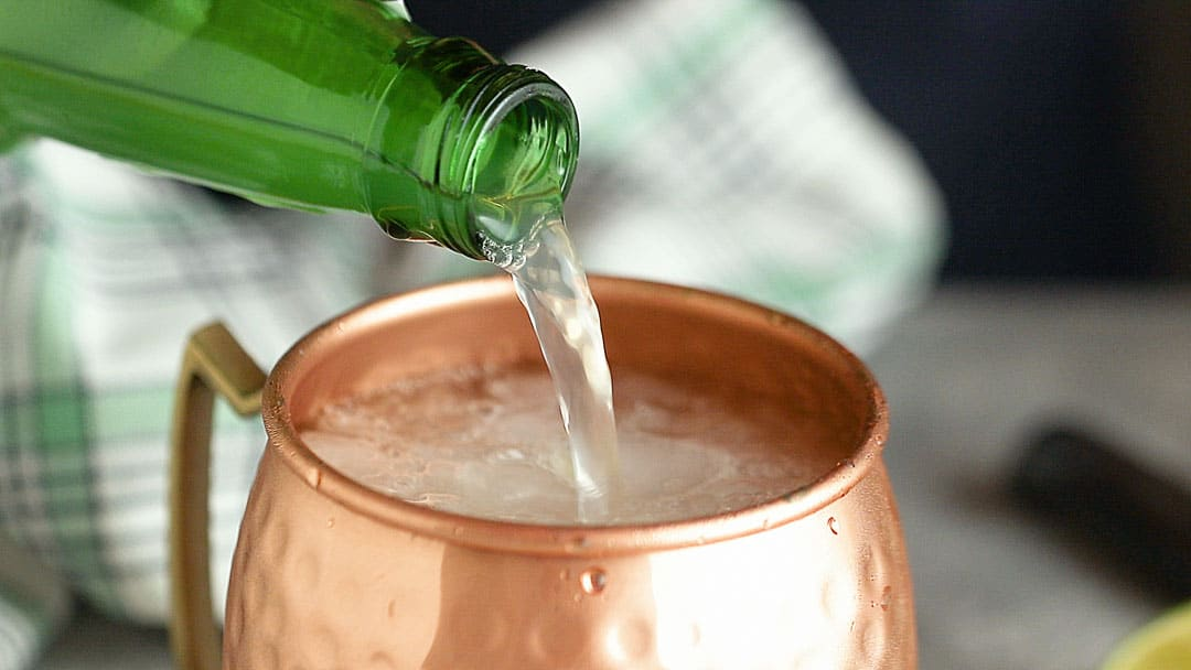 Pouring ginger beer into a Moscow mule cocktail.