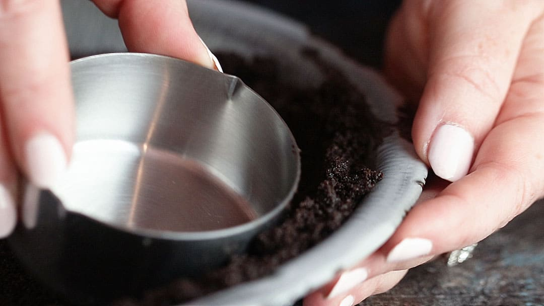 Close up image of shaping Oreo pie crust with a measuring cup.
