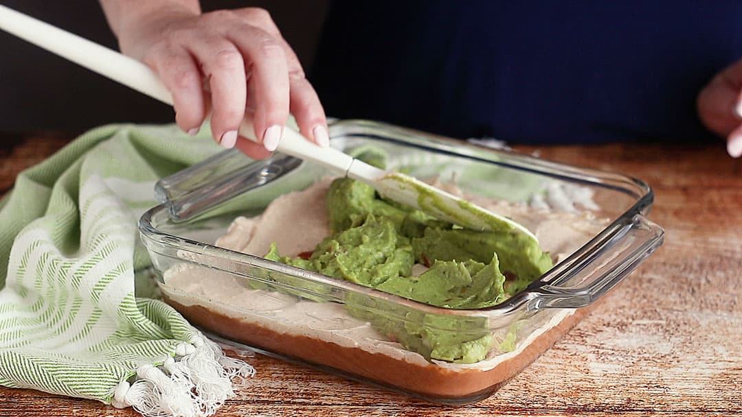 Spreading guacamole over seasoned cream cheese.