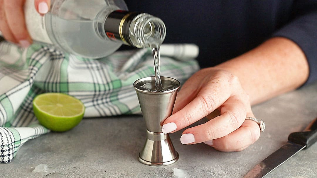 Measuring vodka into a stainless steel jigger.