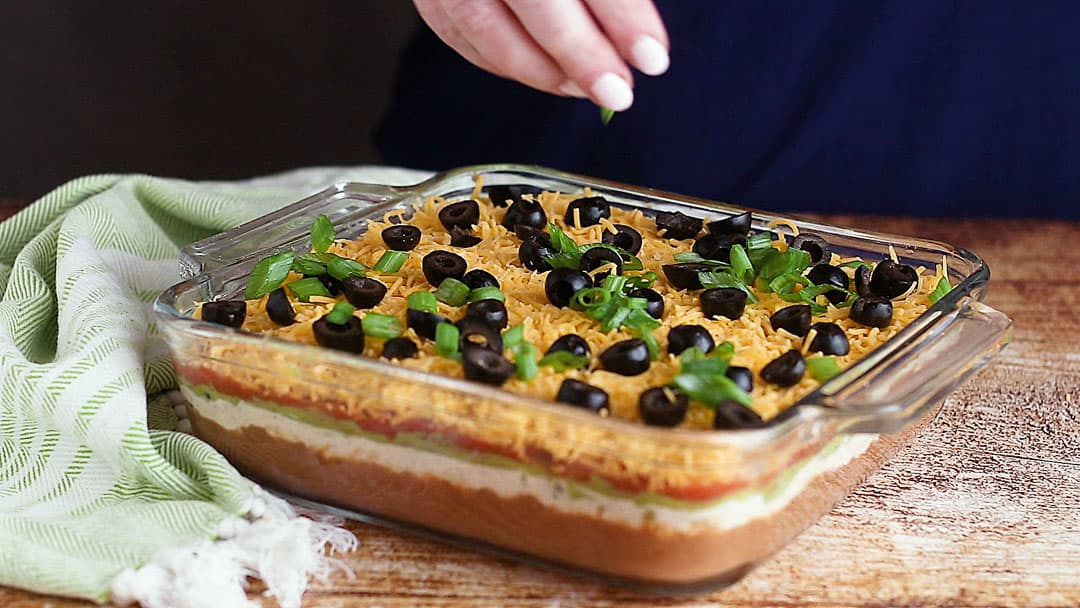 Sprinkling olives and green onions over 7-layer Mexican dip.