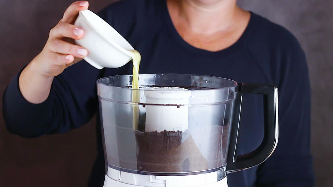 Pouring melted butter over Oreo cookie crumbs.