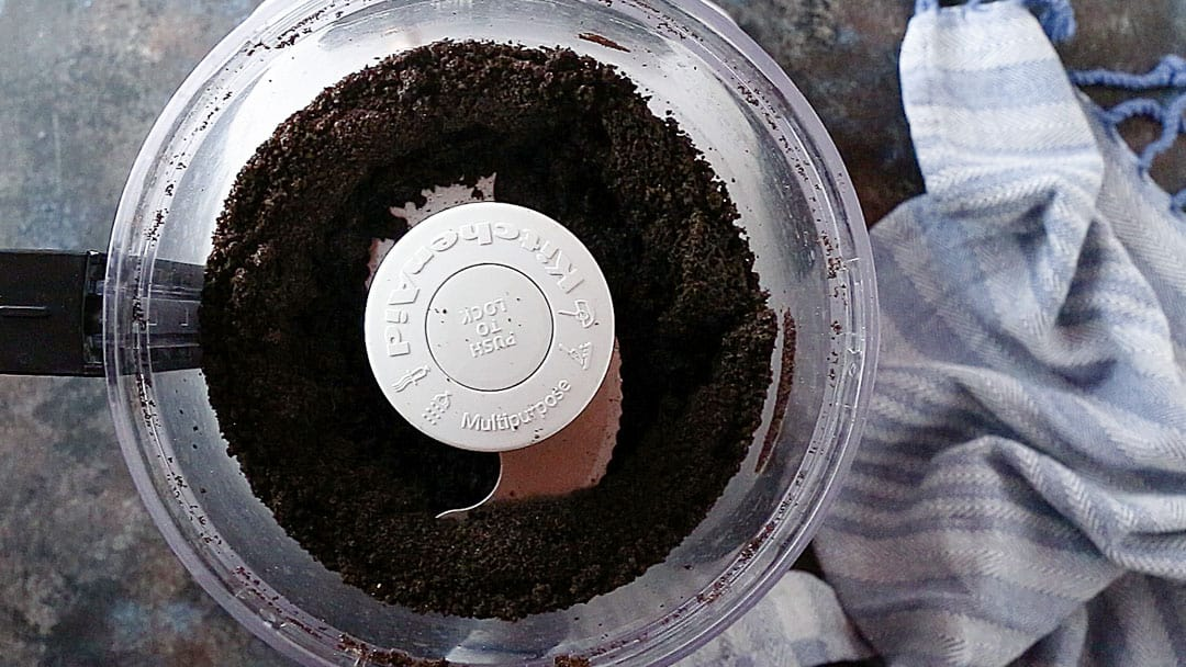 Finely ground Oreo crumbs in the bowl of a food processor.