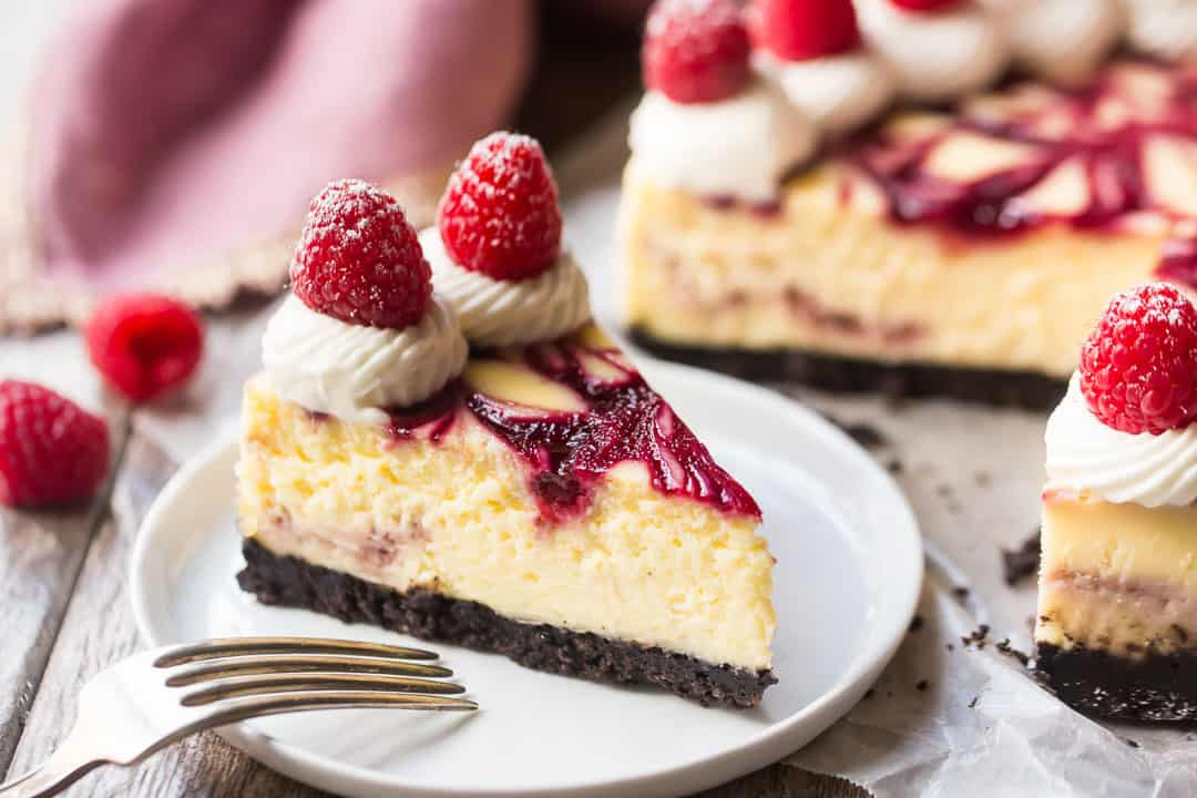 Horizontal image of a slice from a white chocolate raspberry cheesecake, with a pink napkin in the background.