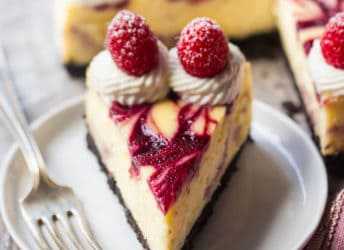 A perfect slice of white chocolate raspberry cheesecake on a white plate, with the whole cheesecake in the background.