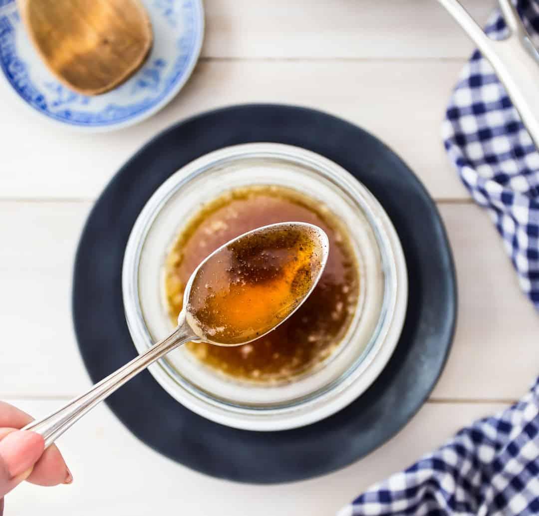 Overhead image of a spoonful of brown butter over a bowl with a blue checkered napkin.