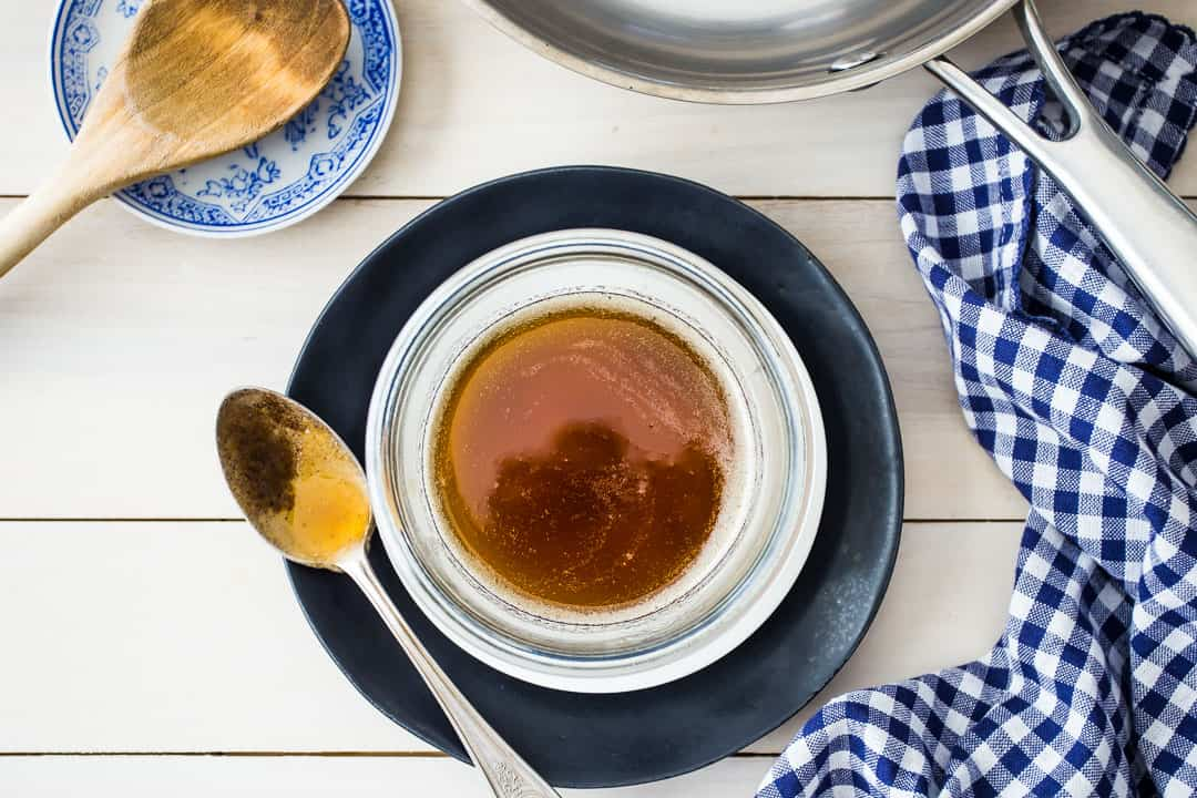 Top down image of a bowl of brown butter, with a silver spoon, a stainless skillet, and a blue checkered napkin.