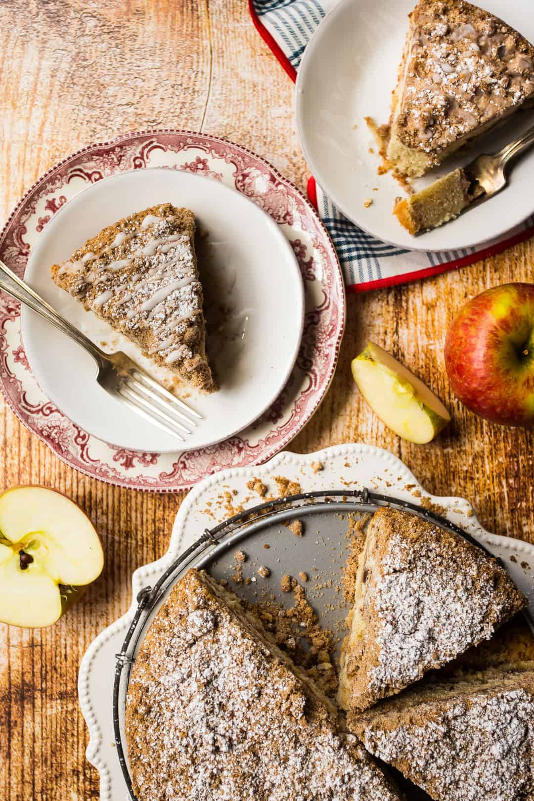 Slices of apple cinnamon coffee cake on plates with fresh apples.