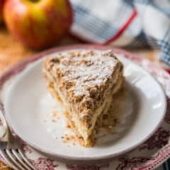 Slice of apple coffee cake on a red patterned plate, with fresh apples in the background.