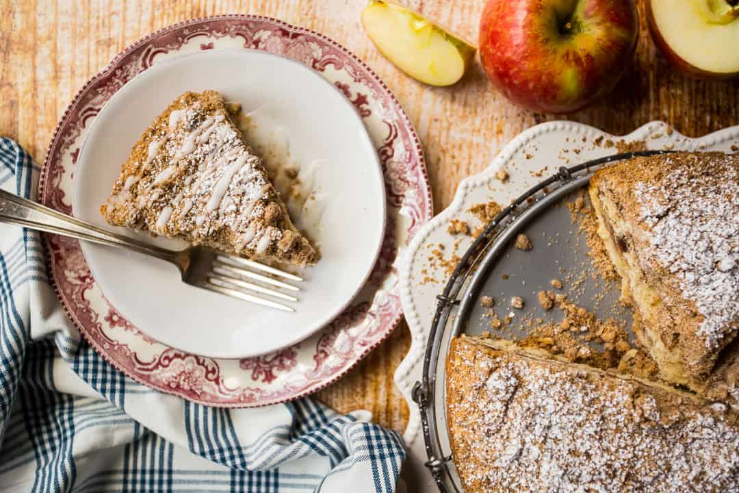 Overhead image of a slice of apple sour cream coffee cake, with the whole cake off to one side.