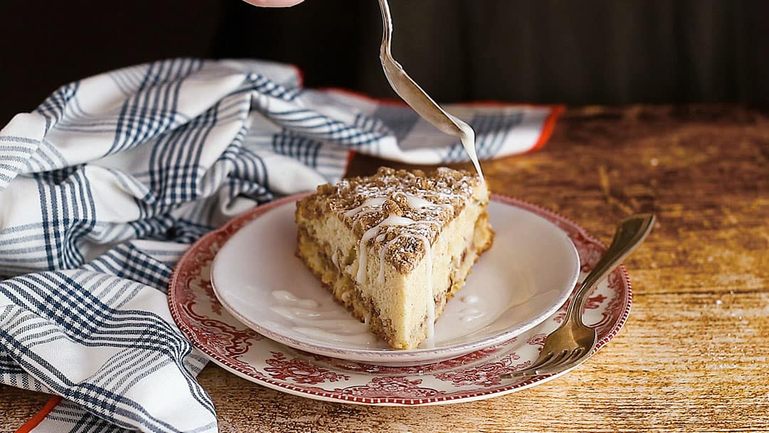 Drizzling icing over a slice of fresh apple coffee cake.
