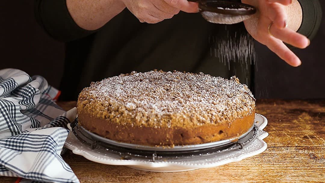 Dusting apple coffee cake with powdered sugar.