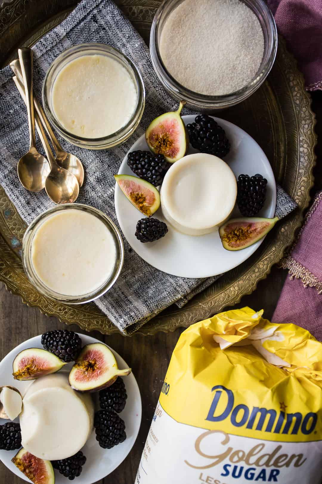 Classic panna cotta recipe, on a wooden table with golden sugar and small gold dessert spoons.
