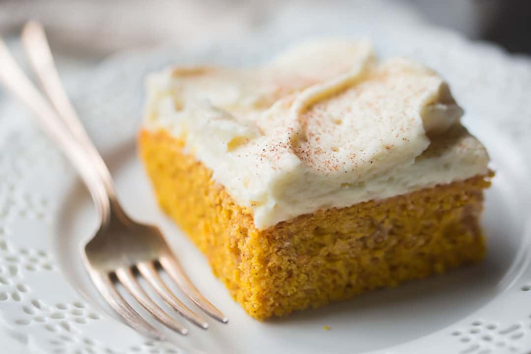 Close up image of a square of moist homemade pumpkin cake on a white plate with a silver fork.