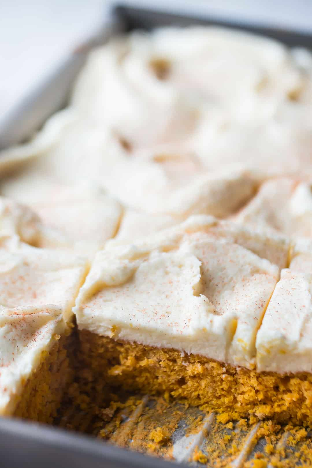Rectangular pan of pumpkin spice cake with swirls of cream cheese frosting, on a pale background.