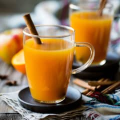 Two glass mugs of hot apple cider with cinnamon sticks.