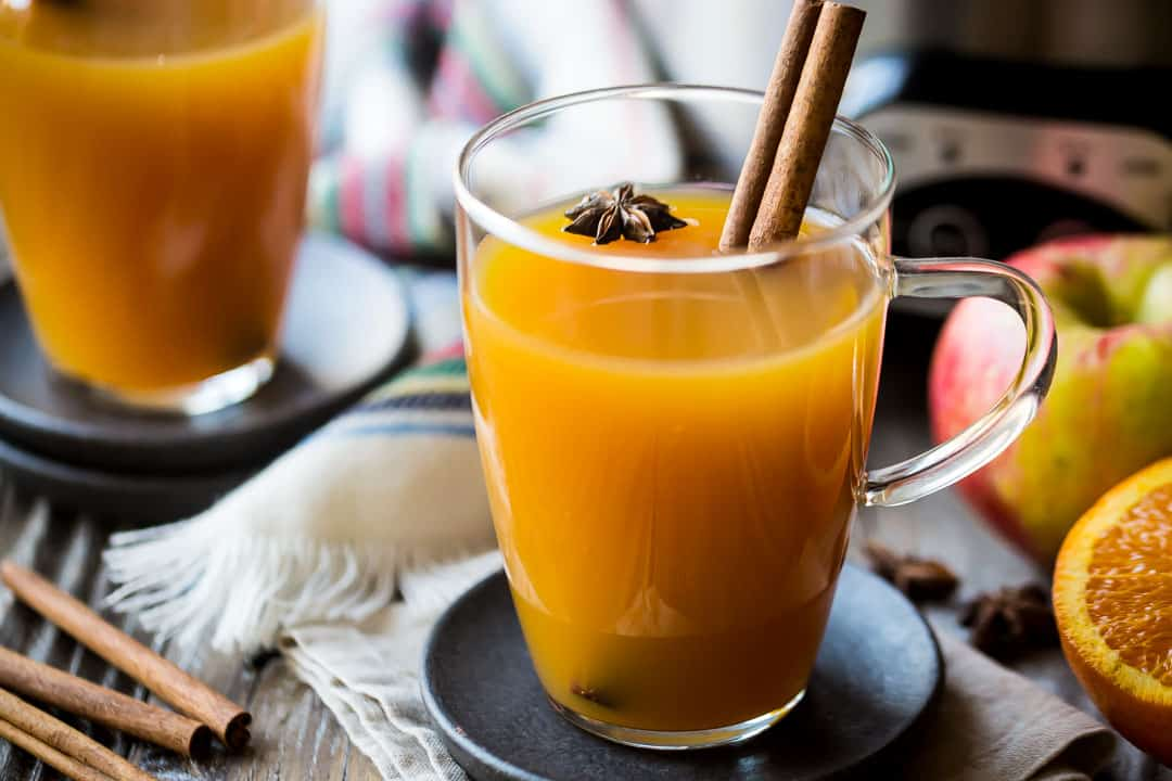 Spiked hot apple cider in glass mugs with apples, oranges, and cinnamon sticks in the background.