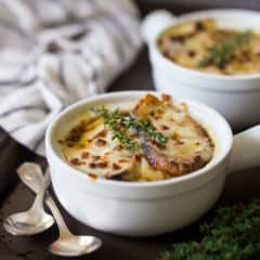 French onion soup in a white ceramic crock on a dark brown tray with vintage silver spoons.