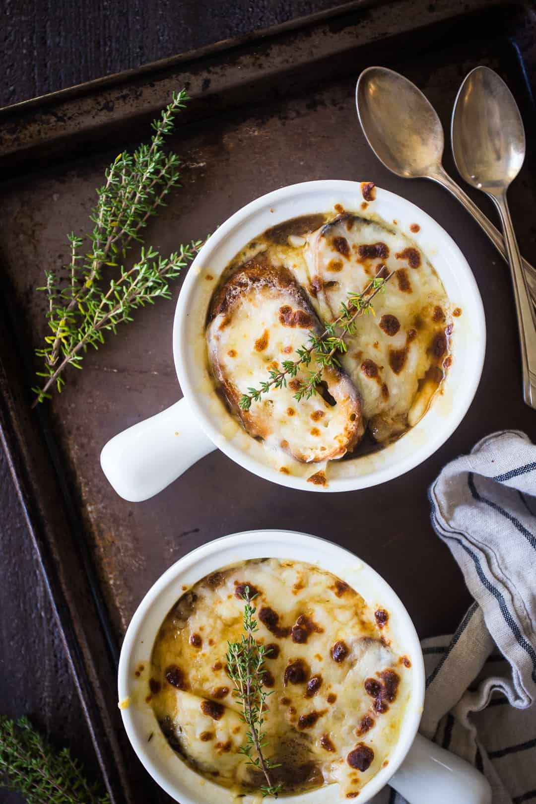Overhead image of two bowls of French onion soup on a brown tray with a striped cloth, vintage silver spoons, and a sprig of fresh thyme.