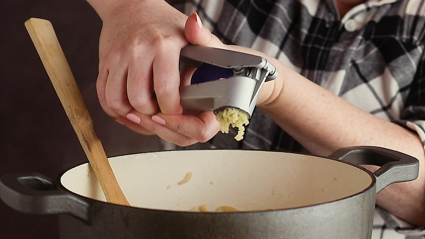Pushing garlic through a garlic press and into a pot of French onion soup.