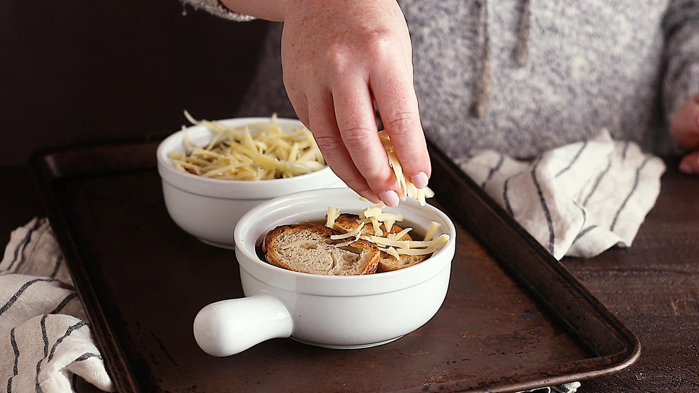 Topping French onion soup with cheese.