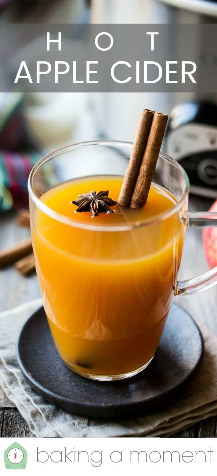 """Mulled cider in a glass mug with cinnamon, citrus, and spices, with a text overlay above reading """"Hot Apple Cider."""""""