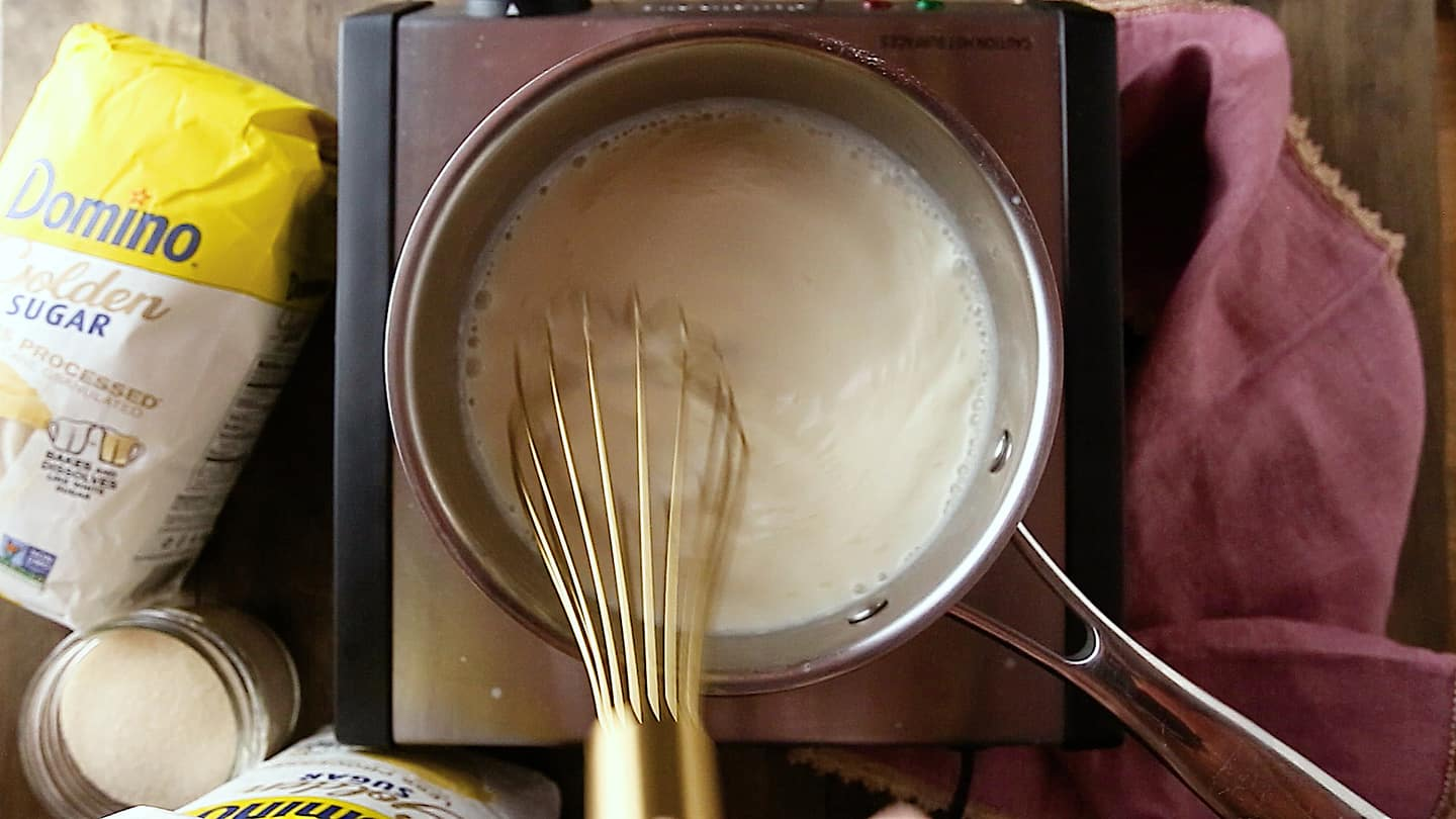 Making panna cotta: Whisking the mixture to eliminate lumps.