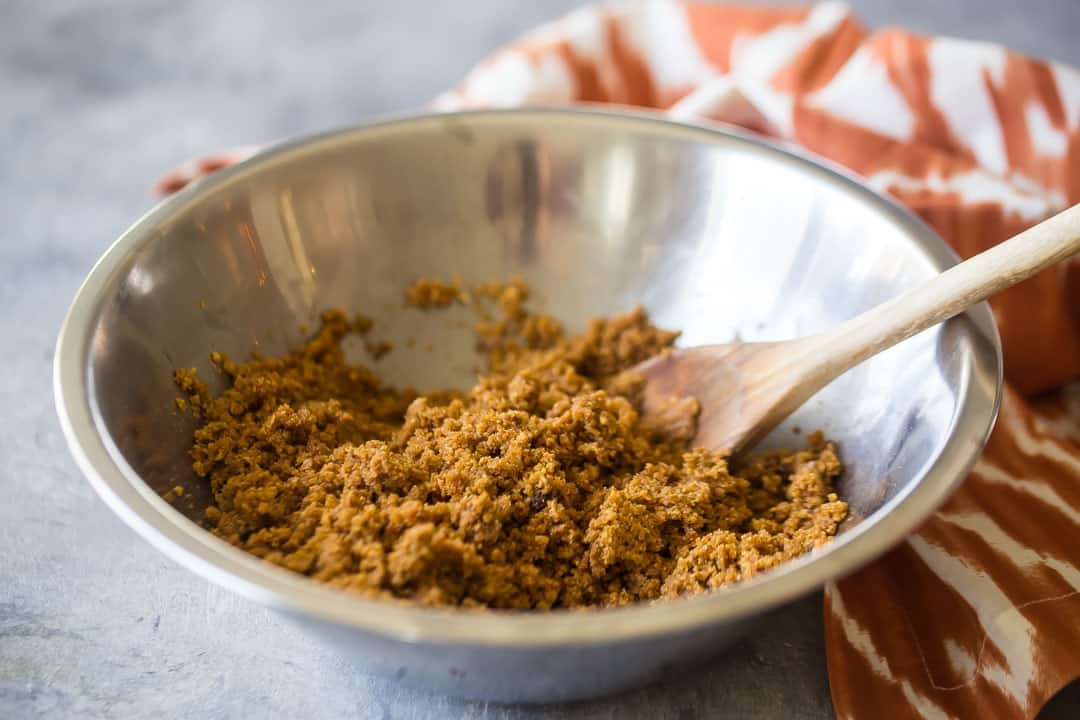 Mixing graham cracker crust together with a wooden spoon.