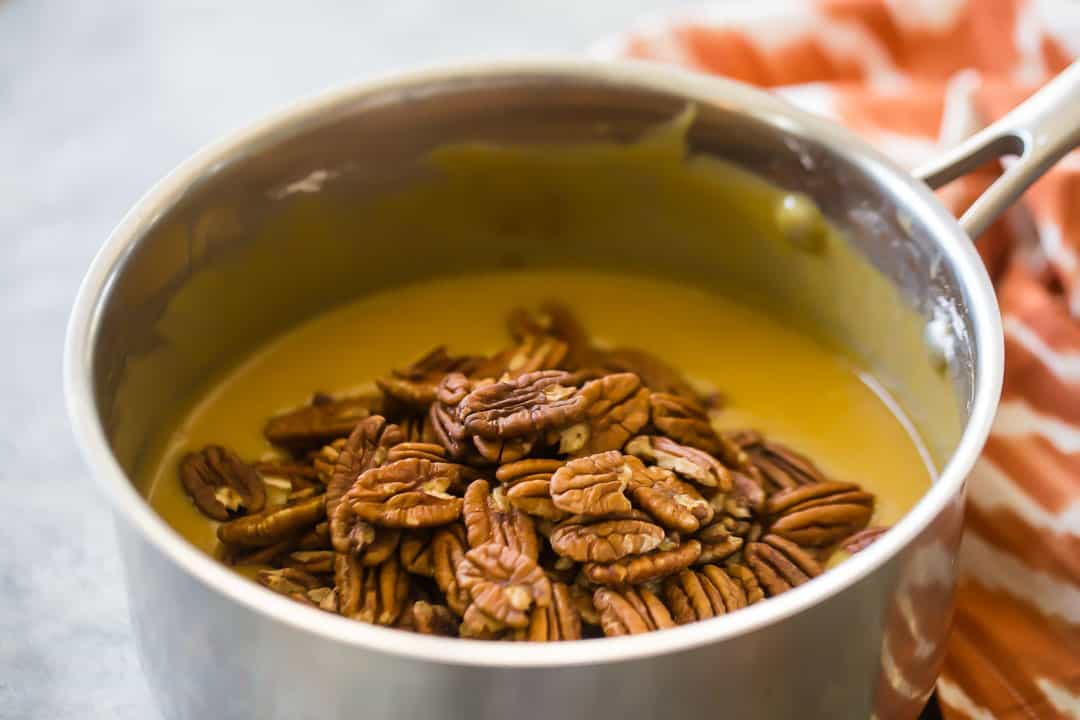 Adding pecans to stove top pecan pie filling.
