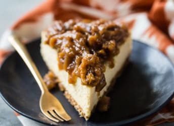 Slice of pecan pie cheesecake on a dark plate with a gold fork.