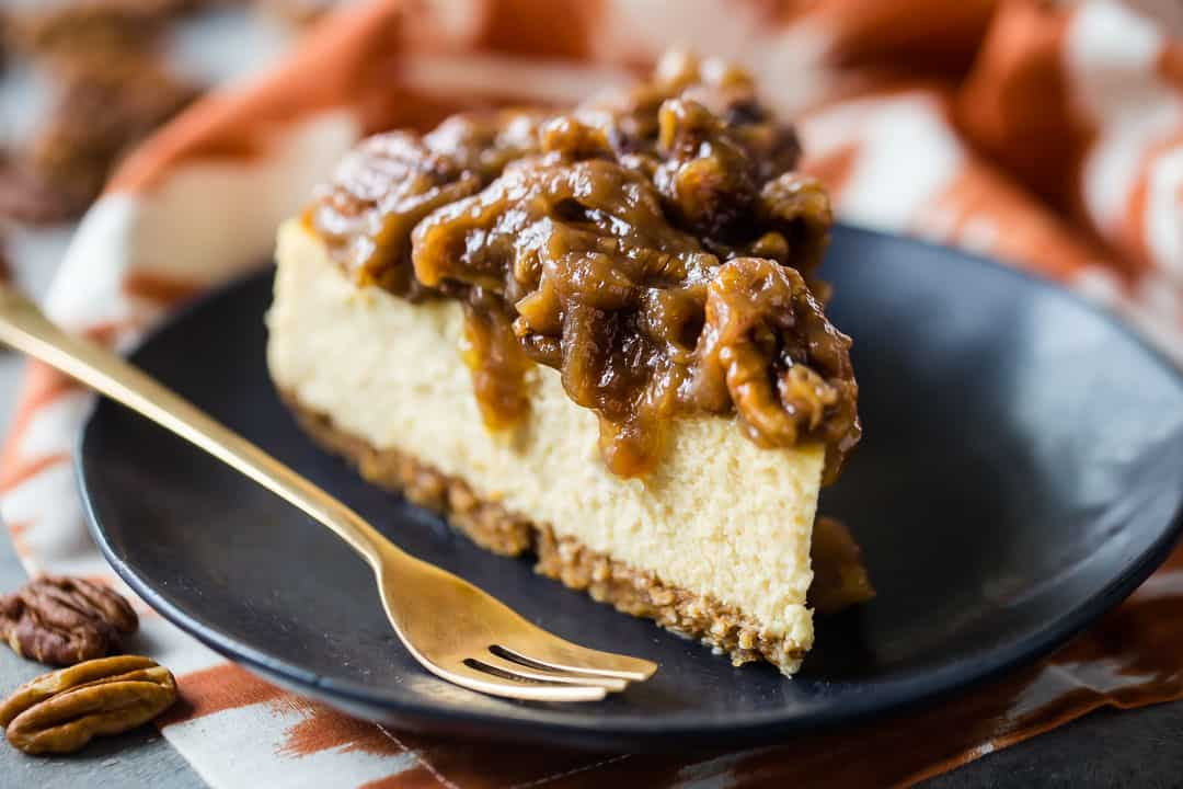 Slice of pecan pie cheesecake on a dark plate with an orange printed cloth in the background.