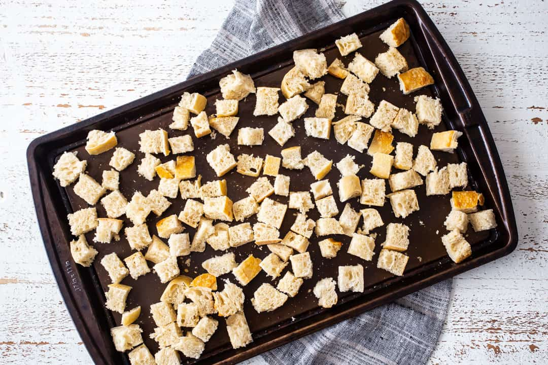 Dry cubes of bread on a baking sheet.