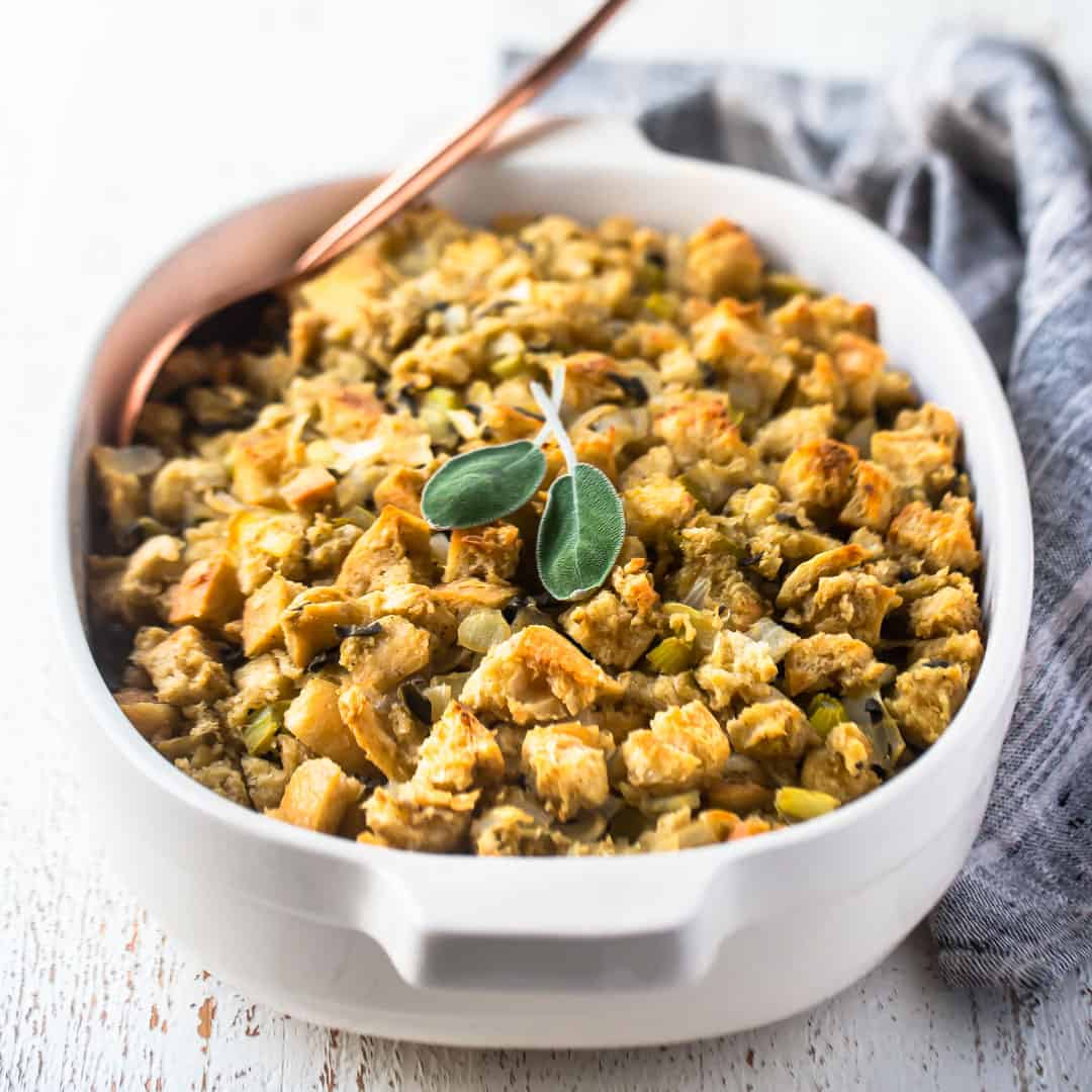 Thanksgiving stuffing recipe baked in a white casserole dish with fresh sage and a gray cloth in the background.