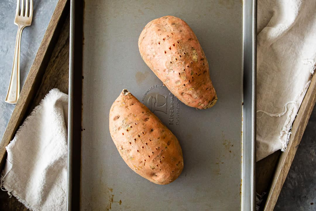 Two sweet potatoes on a sheet pan.