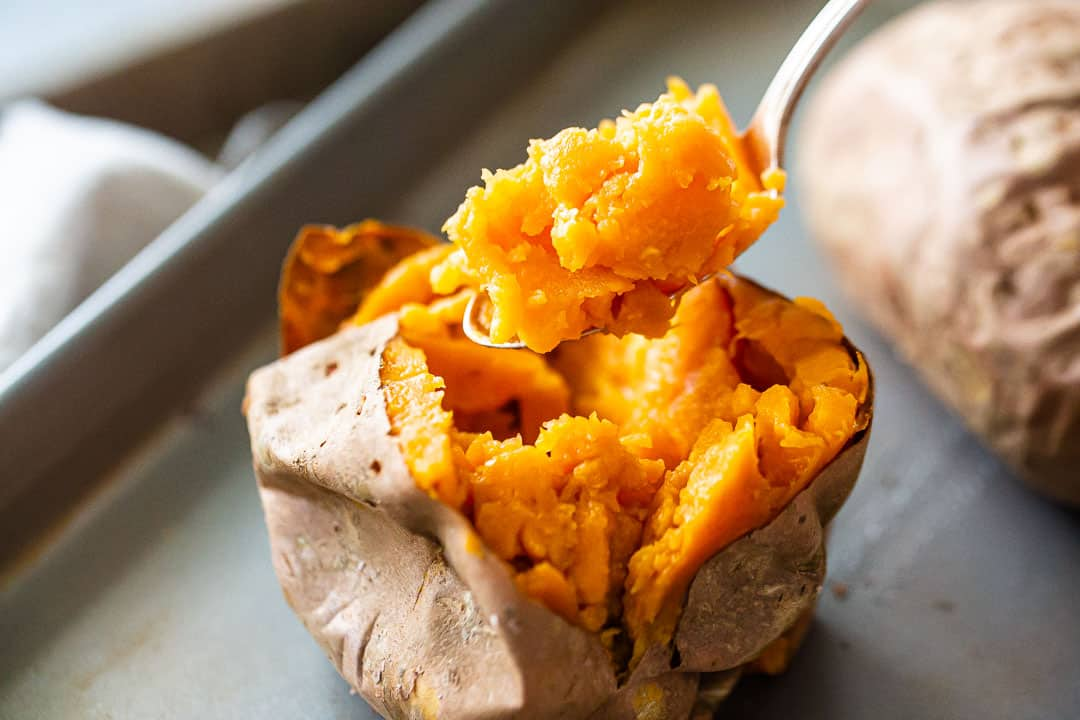 Scooping the flesh out of a roasted sweet potato with a spoon.