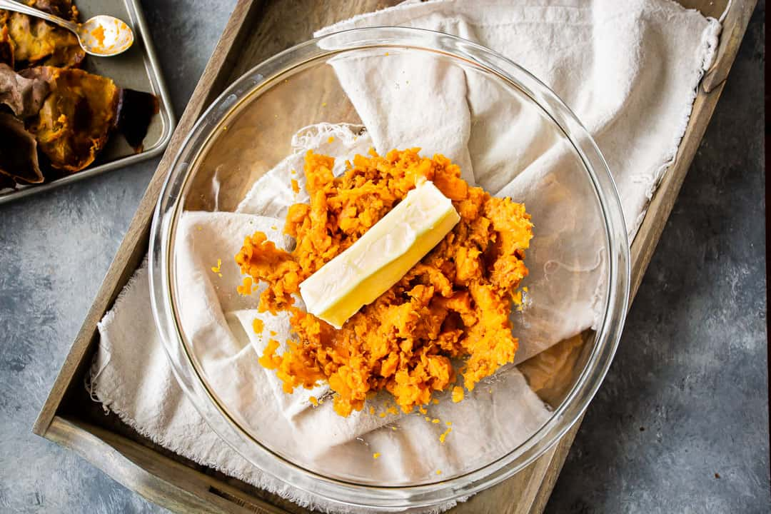 Mashed roasted sweet potatoes and softened butter in a glass bowl, for making sweet potato pie.