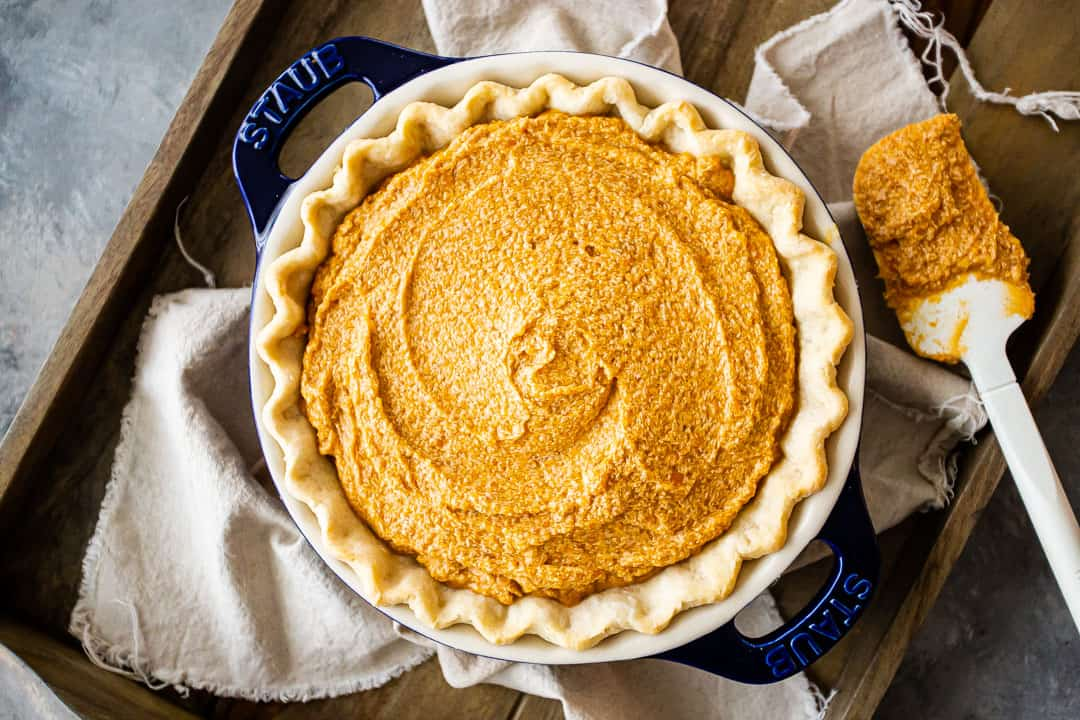 Unbaked sweet potato pie on a baking sheet with a linen cloth.