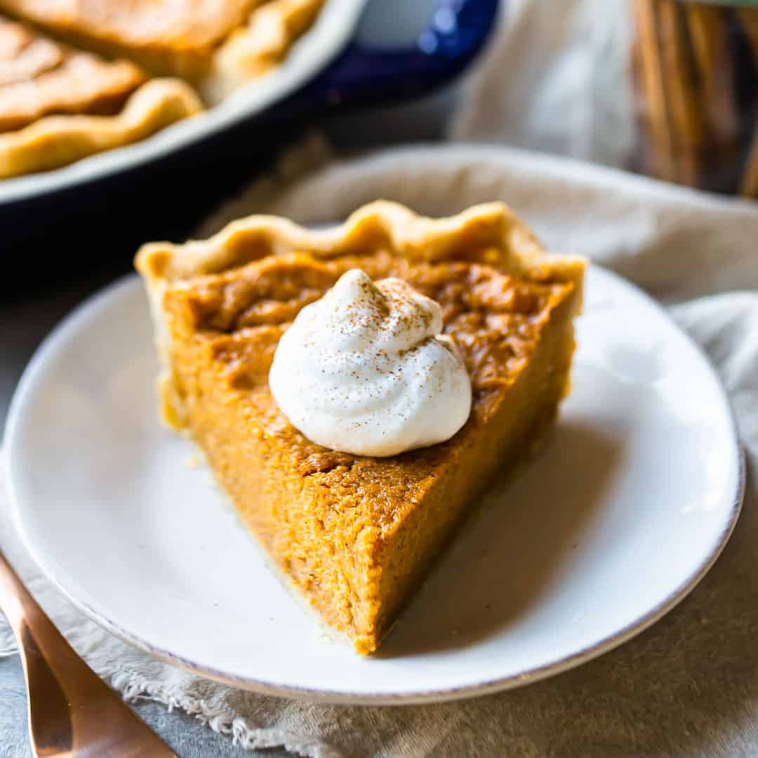 A slice of sweet potato pie on a white plate, with whipped cream and cinnamon.