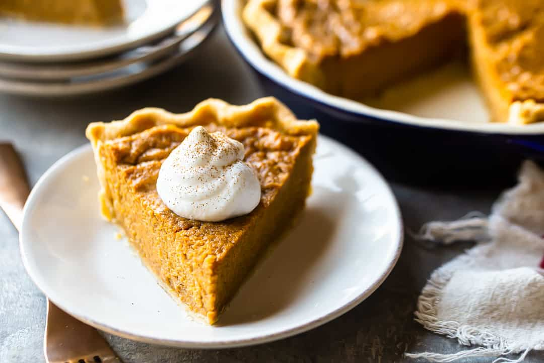 Slice of southern sweet potato pie, with the whole pie and some serving plates in the background.