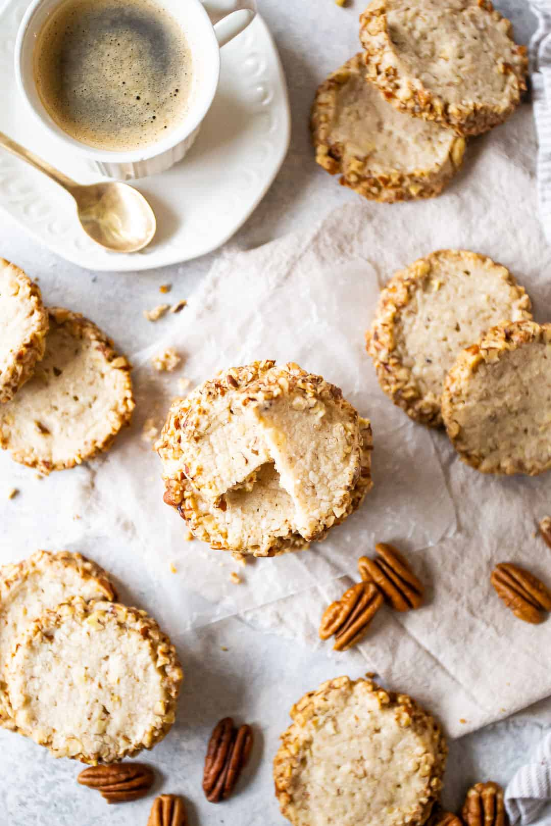 Overhead image of homemade pecan sandies cookies stacked and scattered with pecans and a cup of espresso.