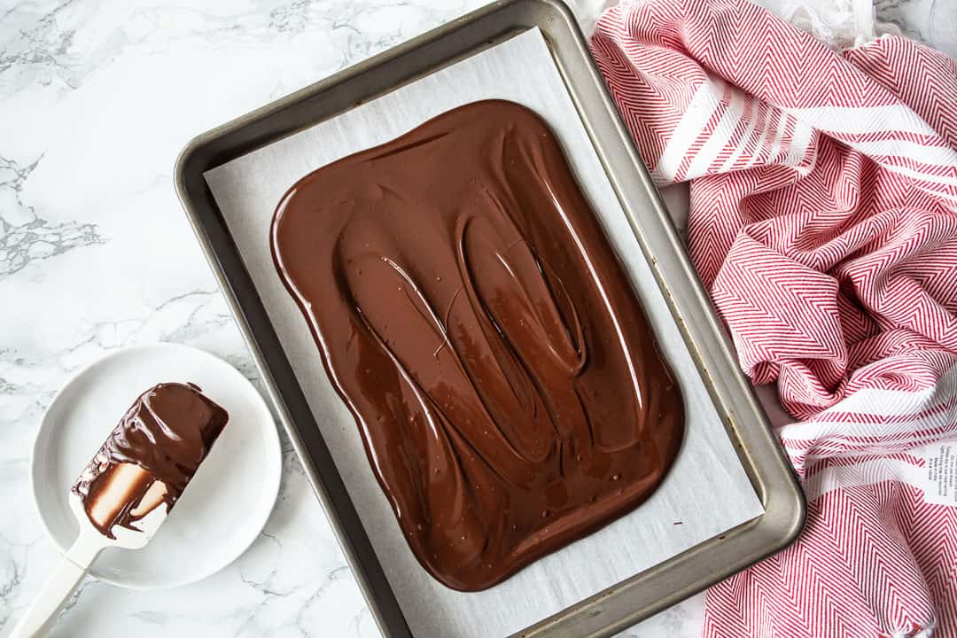 Making chocolate bark with melted chocolate on a baking sheet.