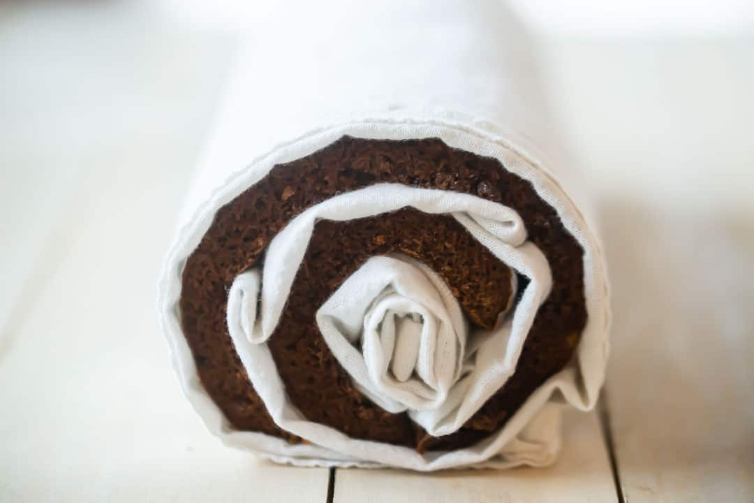 Chocolate yule log cake rolled with a towel.