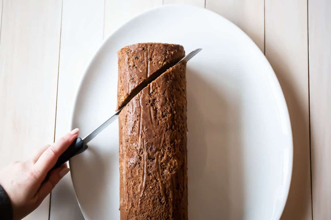 Trimming buche de noel cake with a serrated knife.