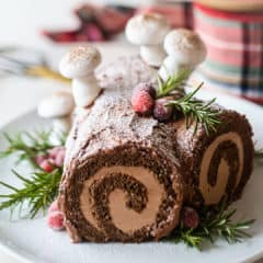 Yule log cake garnished with greens & berries, on a white platter.